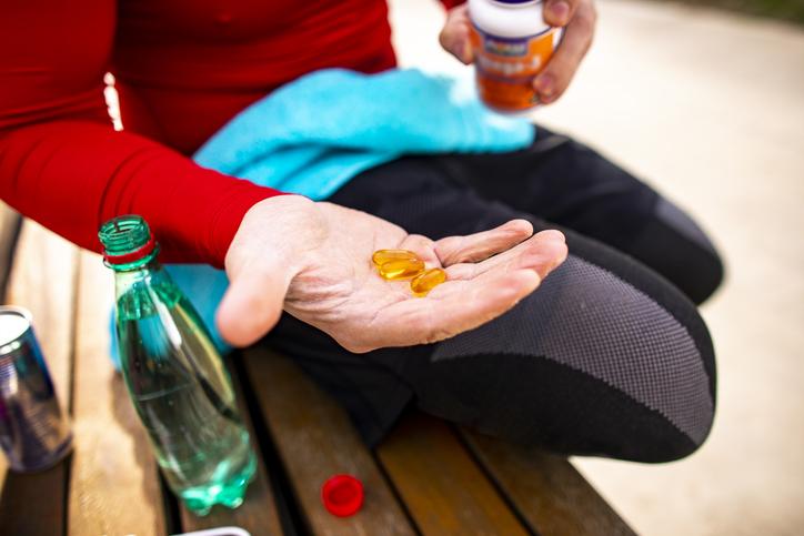 atleta, tenencia, píldoras, en, un, banca de parque - coq10 - la salud del corazón