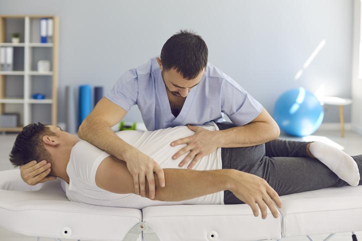 Quiropráctico, osteópata, fisioterapeuta o terapeuta manual que trabaja con un paciente masculino