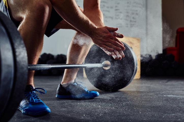 levantamiento de pesas - Levantador de pesas aplaudiendo antes de entrenar con barra en el gimnasio