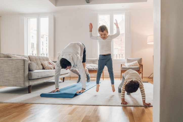 Father with children exercising at home - burpees - hiit exercises at home with family