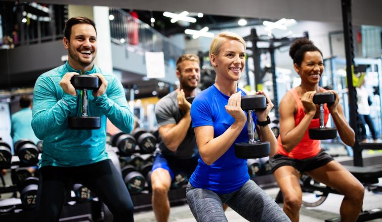 Grupo de personas diversas construyendo fuerza con pesas en el gimnasio.