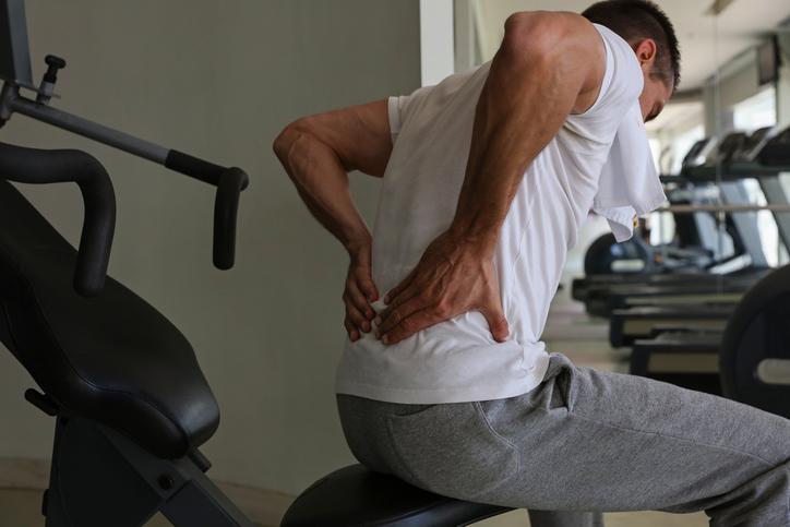 Hombre con lesión en la espalda baja en el gimnasio de halterofilia