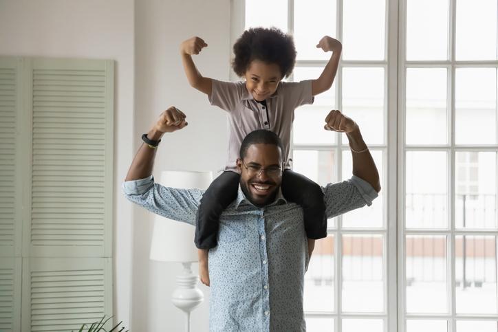 fuerte y sano - Hijo de etnia africana sentado sobre los hombros de los padres mostrando bíceps