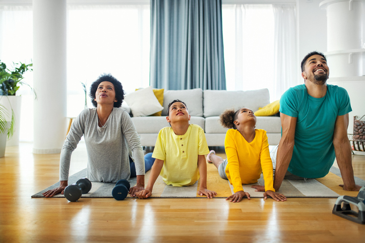 Familia haciendo yoga en casa - metas de salud