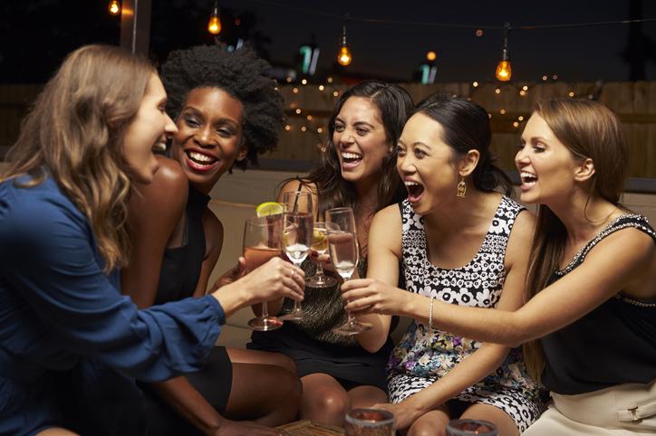 Grupo de amigas disfrutando de la noche en el bar de la azotea; celebrando el éxito; metas de salud
