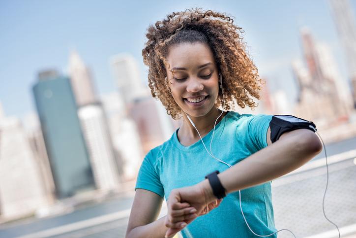 Mujer deportiva rastreando su progreso en el entrenamiento con un reloj inteligente y usando un brazalete para su teléfono celular