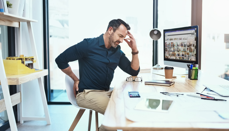 Shot of a mature businessman experiencing back pain while working at his desk with bad posture
