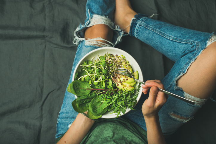 Vegetarian breakfast bowl with greens: spinach, arugula, avocado, seeds and sprouts