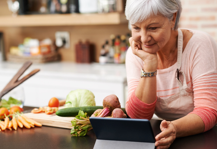 older woman making a healthy recipe with vegetables