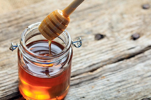 A glass jar with honey on a table - natural sweetener - sugars