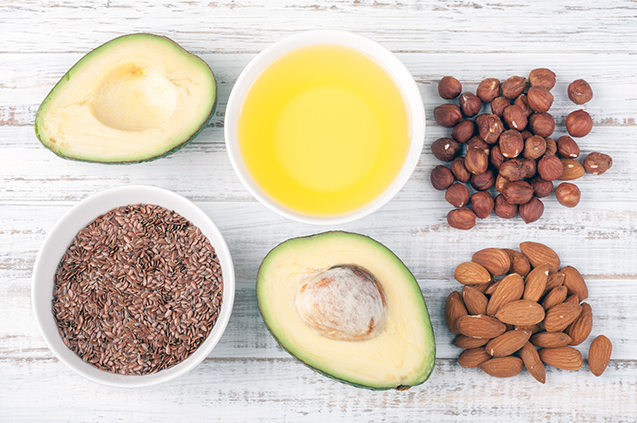 Foods with healthy fats. Sources of omega 3 - avocado, olive oil, nuts and flax seed on wooden background. Healthy food
