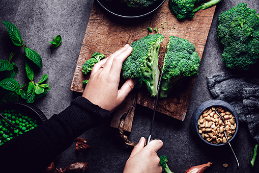 Woman cutting fresh broccoli