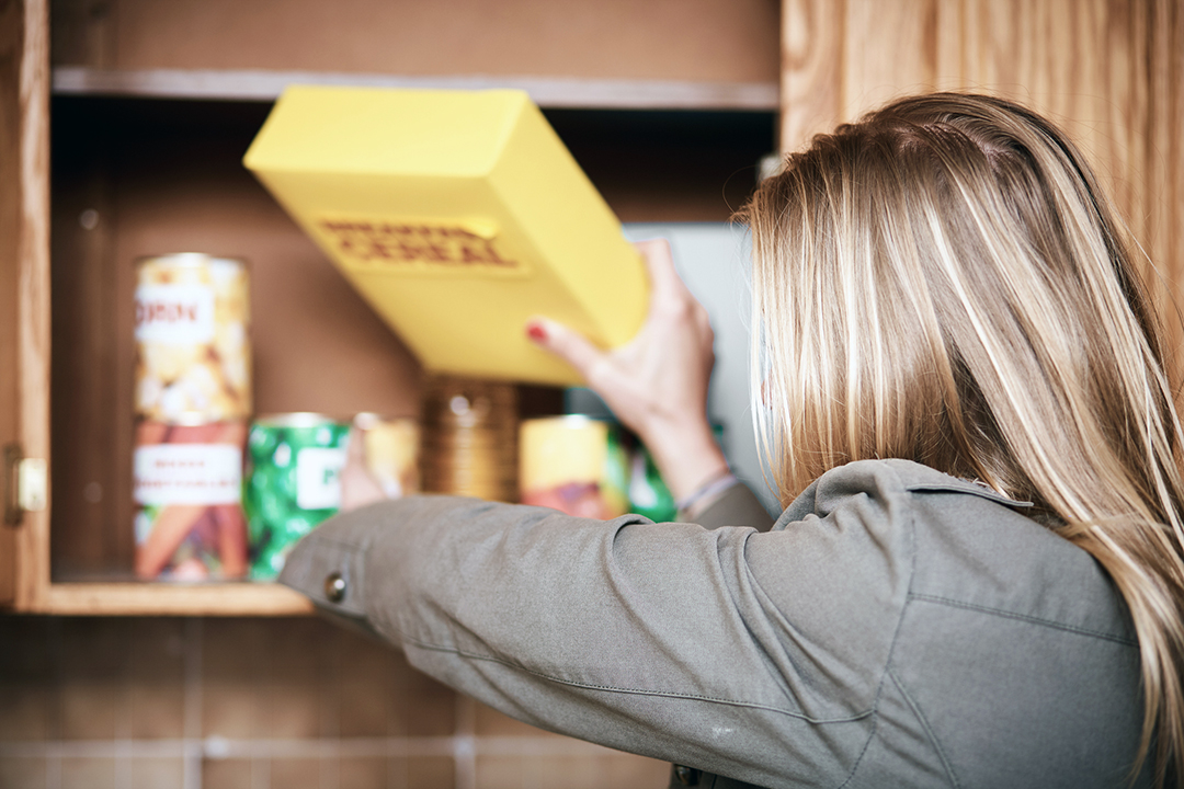 Spring clean kitchen pantry - woman going through processed foods