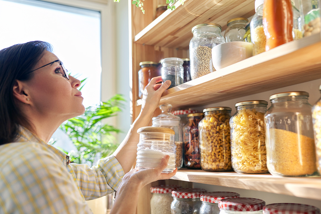 Spring clean kitchen pantry - Food storage in pantry, woman holding jar of sugar in hand. Pantry interior, wooden shelf with food cans and kitchen utensils