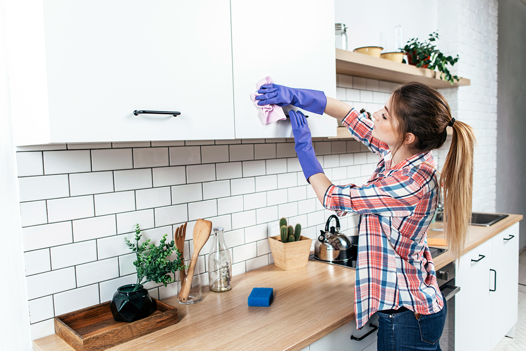 Spring clean kitchen pantry - Woman in gloves cleaning cabinet with rag at home kitchen.