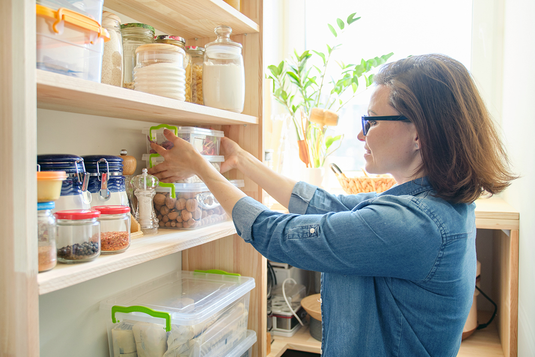 spring clean kitchen pantry - Interior of wooden pantry with products for cooking. Adult woman taking kitchenware and food from the shelves