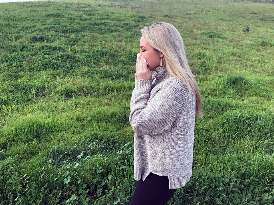 woman playing her nose in a grassy field - seasonal spring allergies sneezing
