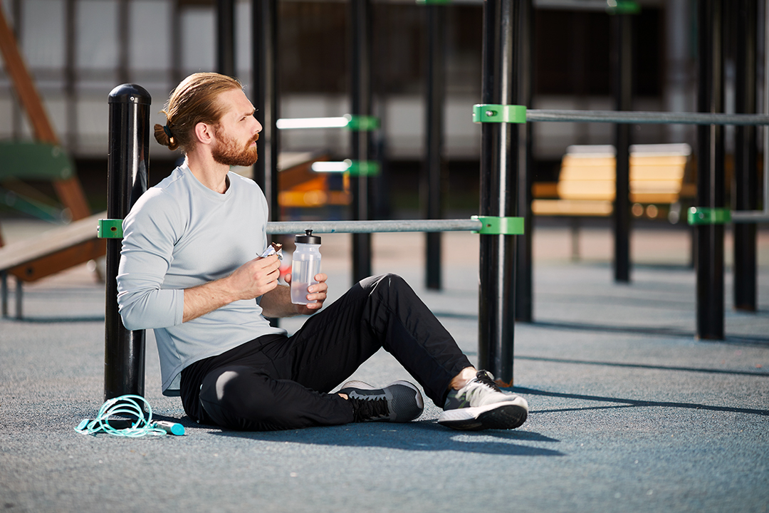 man in sportswear sitting on public sports ground and eating protein snack and drinking water