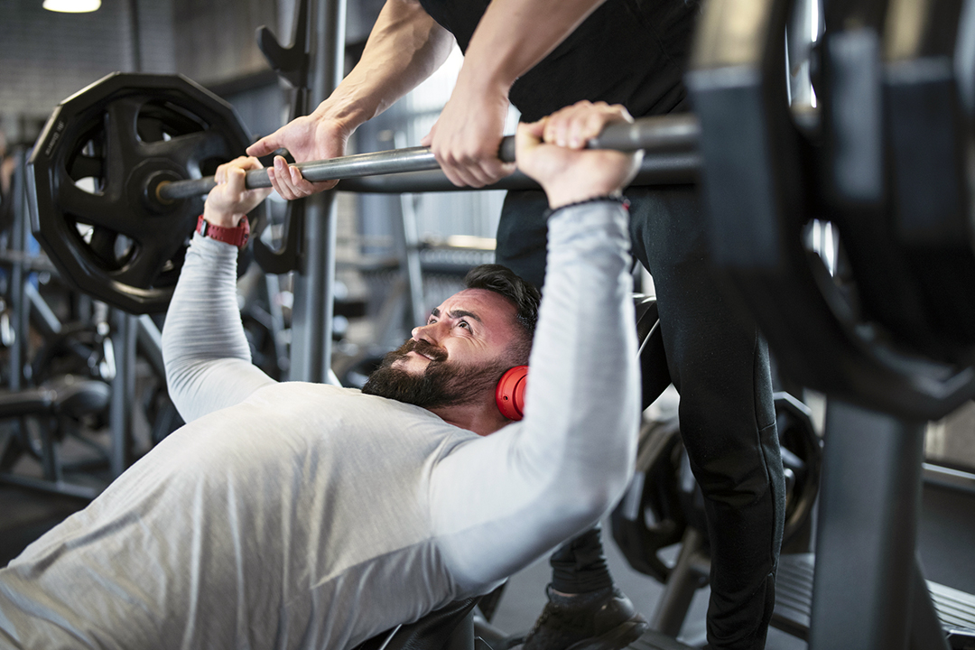 Two friends weightlifting exercising bench press in gym - weights or reps
