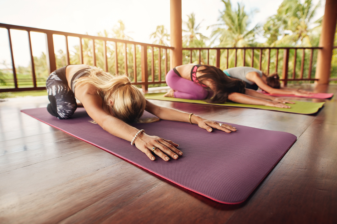 group of women doing morning yoga on outdoor porch - child's pose