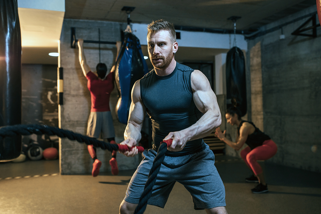 man working out with heavy ropes at the gym - athletes - weight lifting - strength training