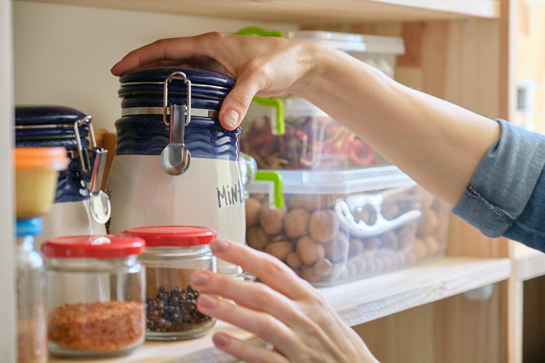 Despensa de cocina limpia de primavera - mujer organizando tarros de cristal
