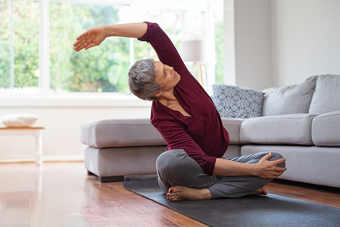 Morning yoga - side bending stretch - mature woman in living room