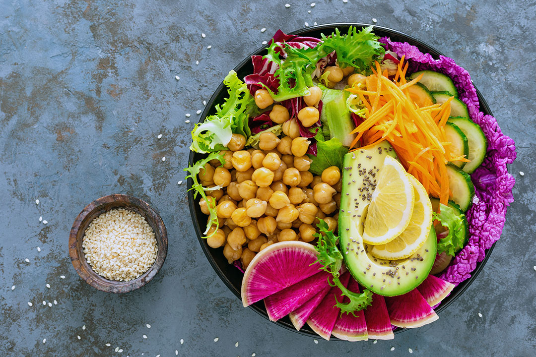 Salad Buddha bowl with fresh cucumber, avocado, watermelon radish, raw carrot, lettuce and chickpea for lunch. Healthy vegetarian food. Vegan vegetable dish.