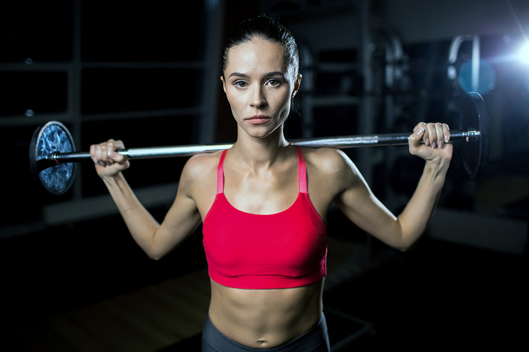 Young active sportswoman holding heavy weightlifting barbell on shoulders during training - strength training