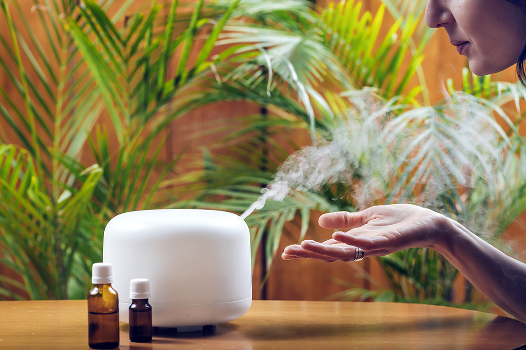 Woman Enjoying Aroma Therapy Steam Scent from Home Essential Oil Diffuser or Air Humidifier - seasonal spring allergy relief