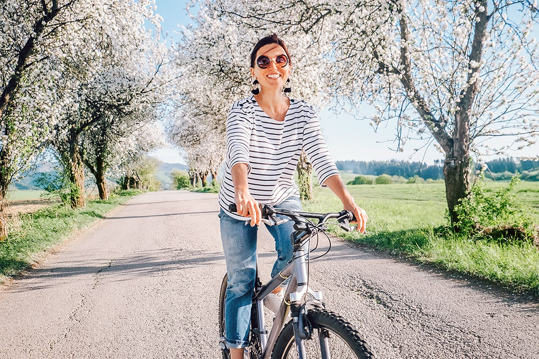 Happy smiling woman rides a bicycle on the country road under blossom trees. Spring is coming - seasonal spring allergies