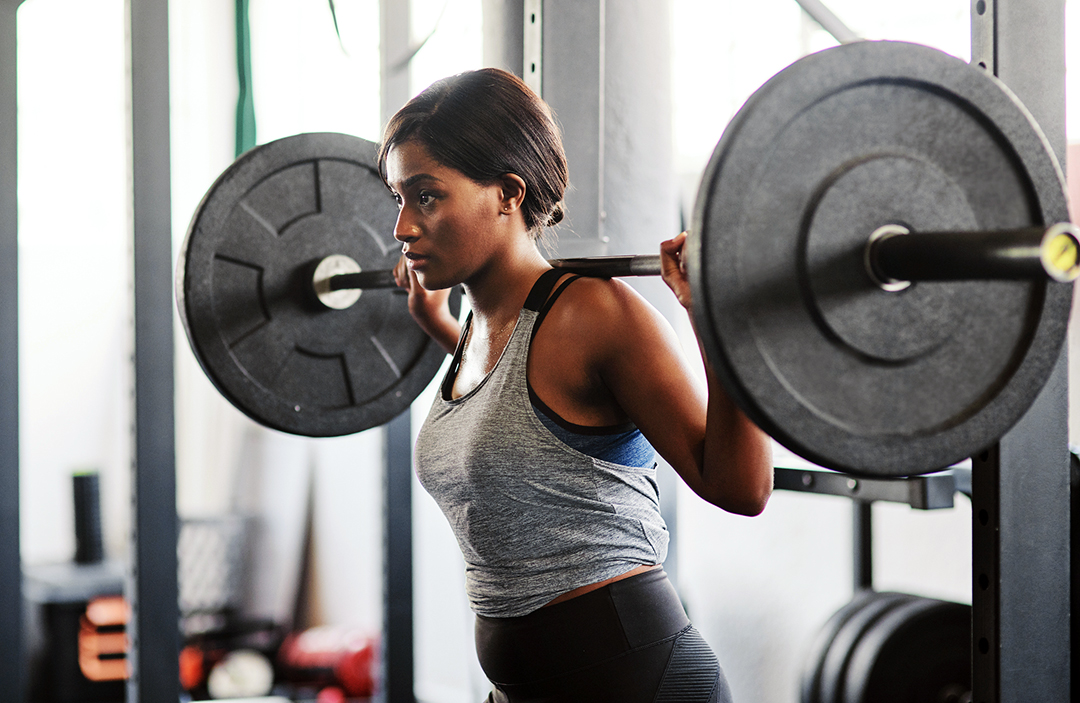 woman weightlifting heavy weights squats - strength training