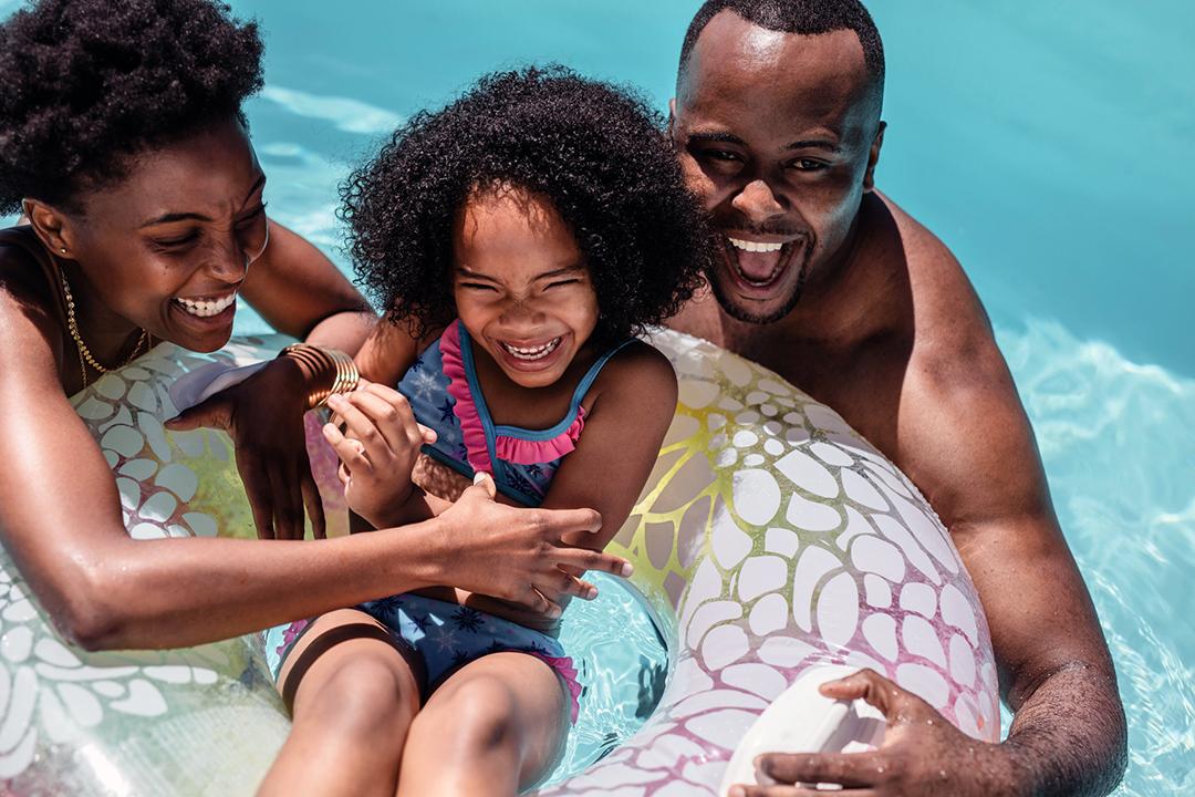 Hombre y mujer negros jugando con su hija en la piscina - temporada de traje de baño