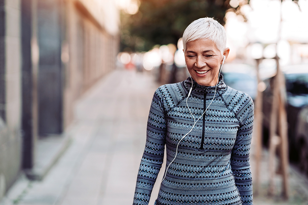 Senior female athlete walking outdoors in the city - Bone health - osteopororsis prevention