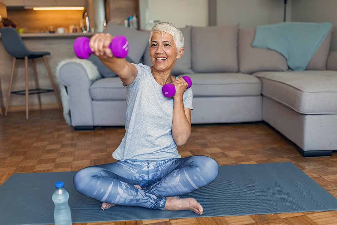 Senior Woman Exercising With Dumbbell At Home