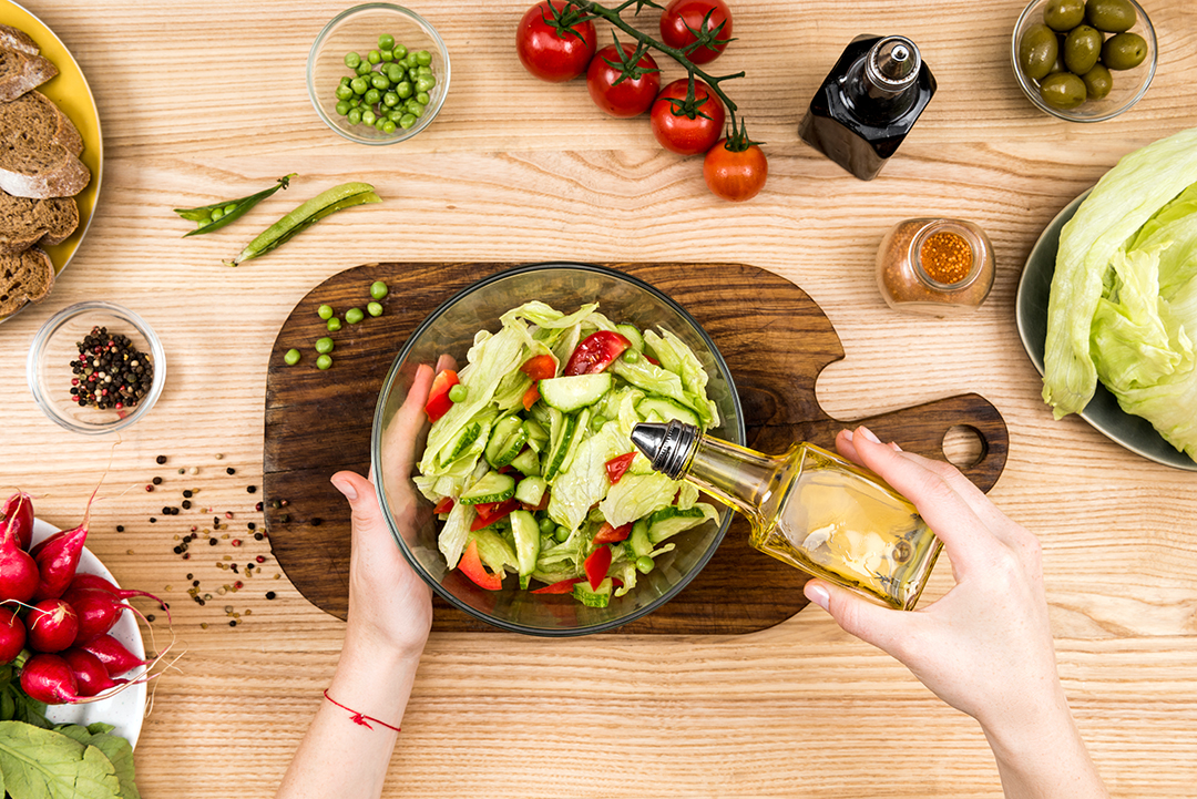 cropped sot of woman pouring olive oil onto fresh vegetables salad