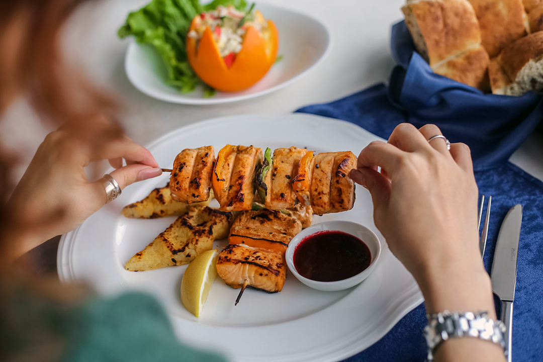 proteína - side view woman eating grilled fish on skewers with sauce and lemon on a plate and bread on the table