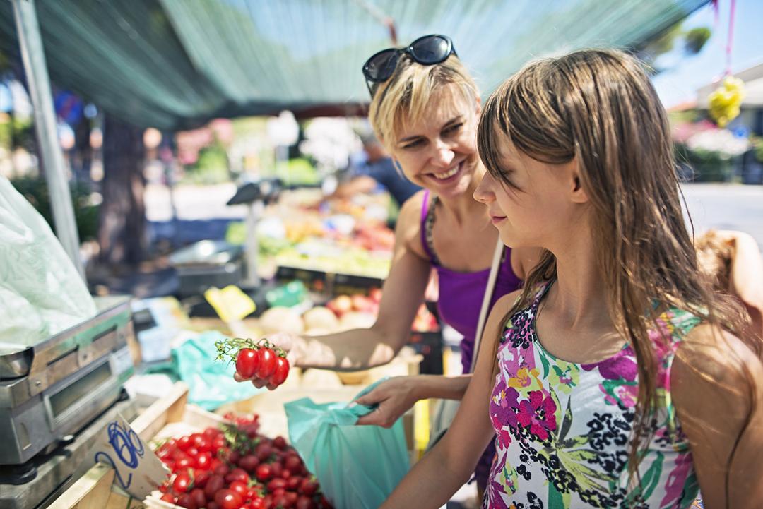 Madre e hija comprando tomates en el mercado del agricultor italiano. pastel de harina de garbanzos. Italia, Toscana.
