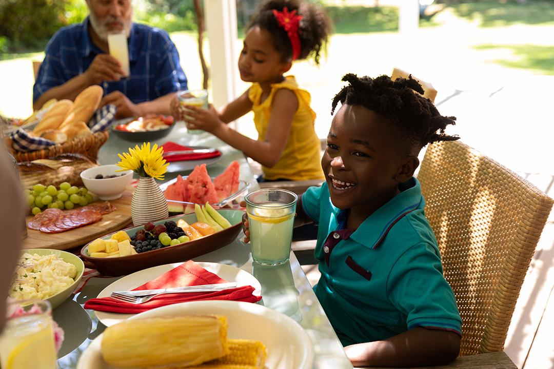 familia comiendo al aire libre con opciones de comidas saludables, frutas y vegetales