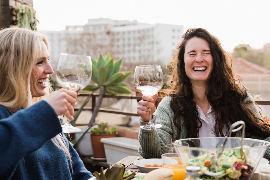 Amigos disfrutando de una comida al aire libre en el balcón del restaurante
