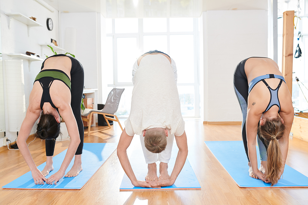 group of women doing a forward bend rag doll pose in yoga studio