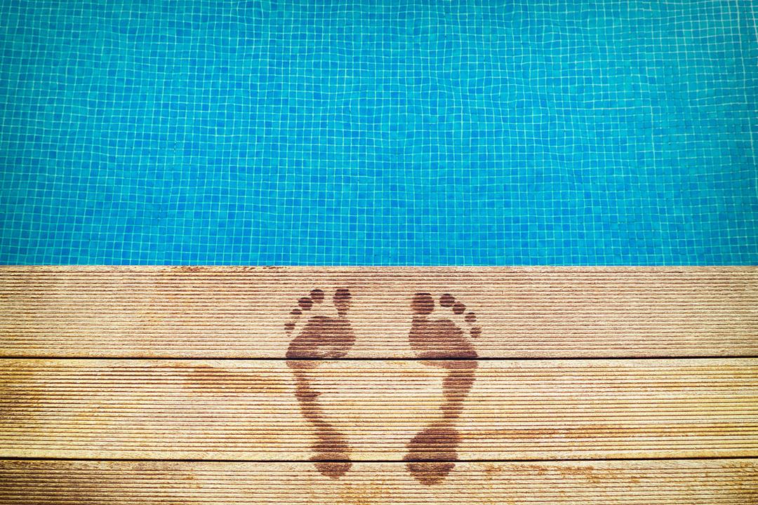 Huellas en la superficie de madera con piscina azul