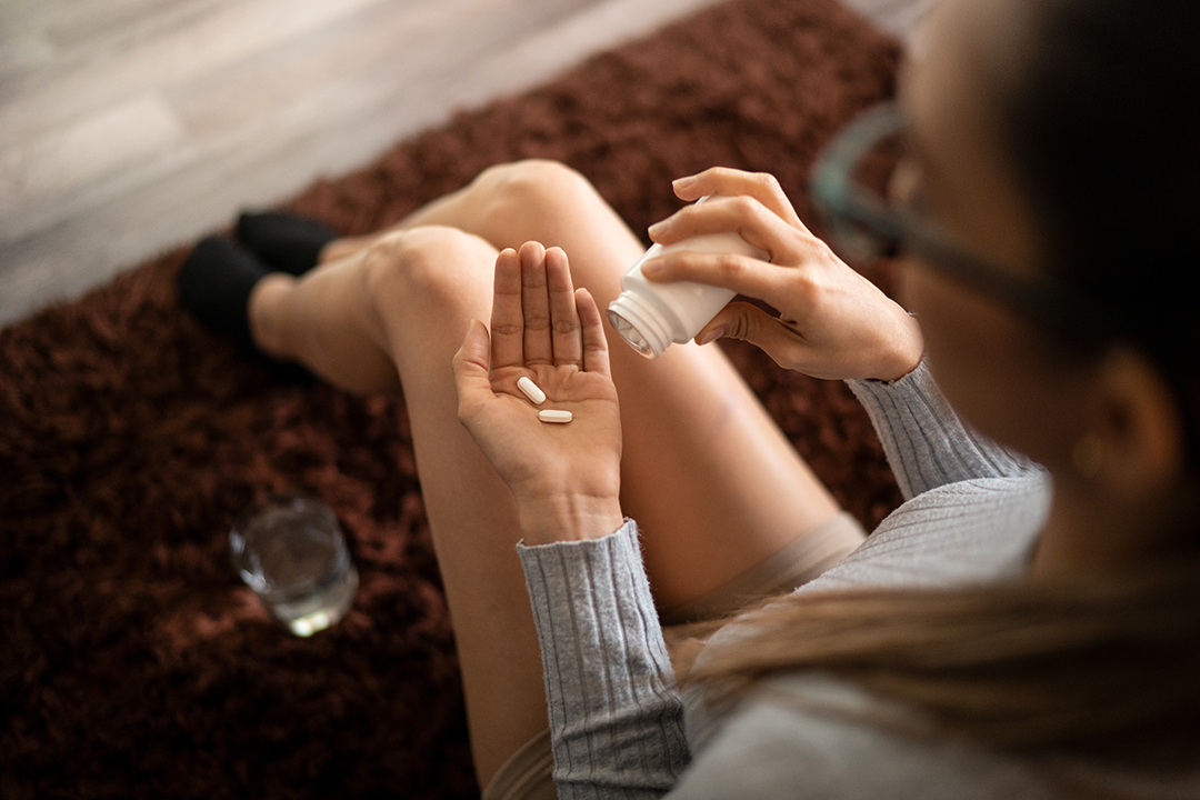 woman taking OTC painkillers for pain relief (NSAID)
