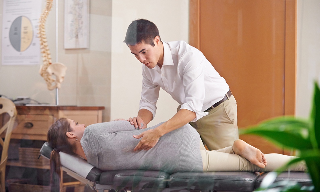 chiropractor adjusting woman - chiropractic care myths and facts