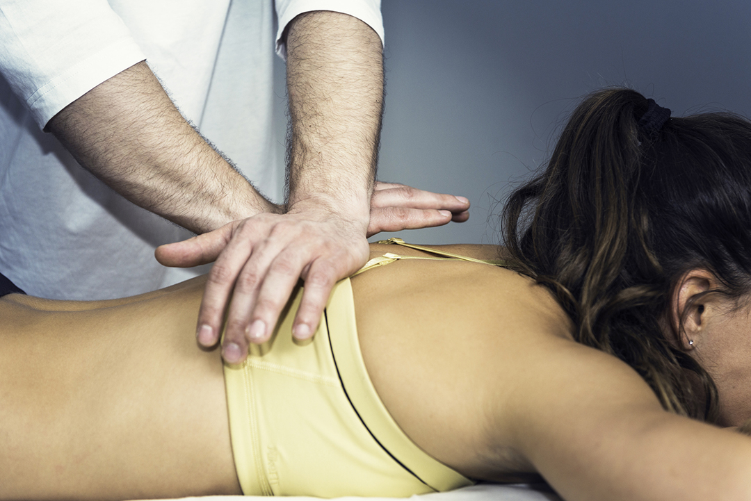 chiropractor adjusting woman's back - chiropractic myths busted