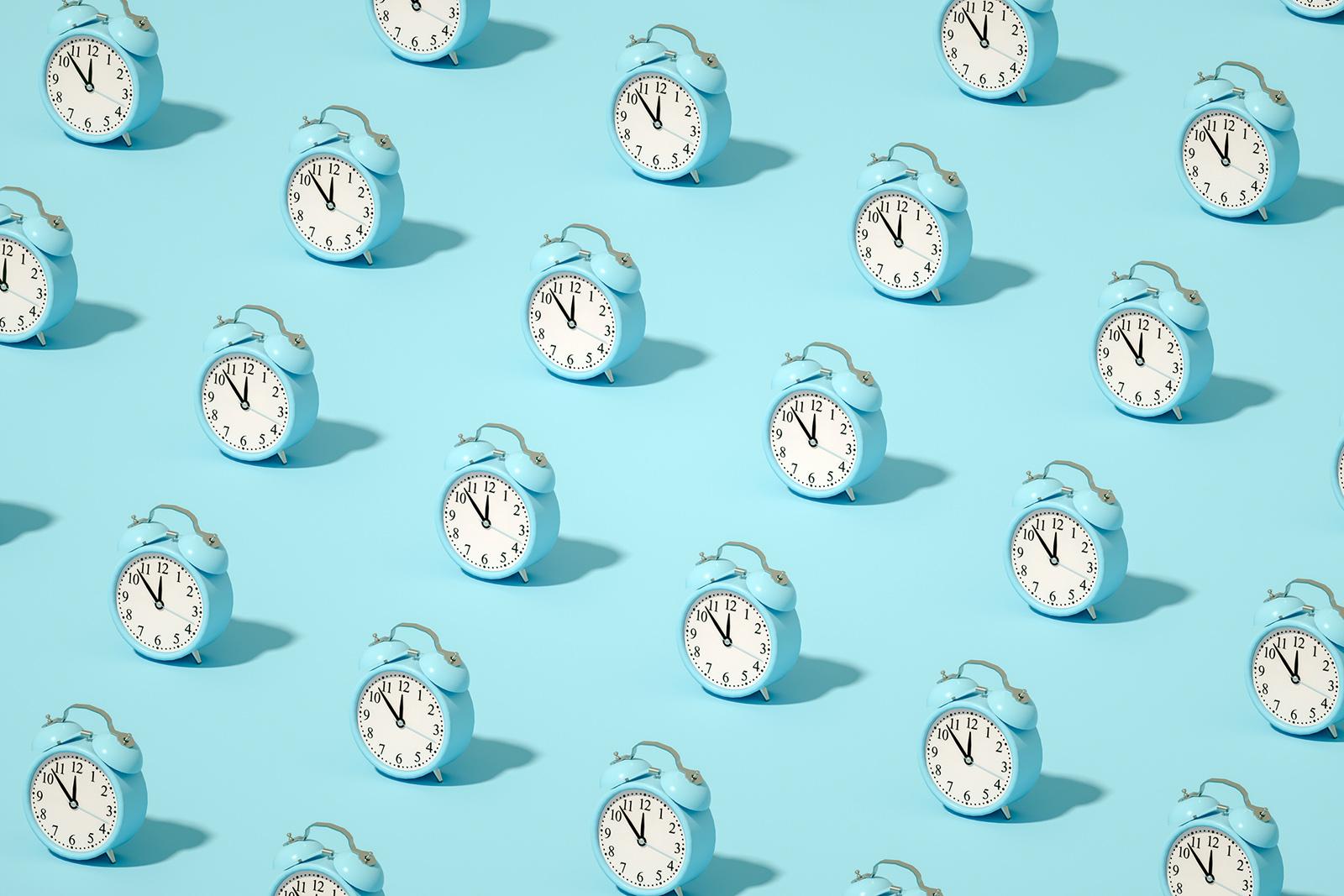 alarm clocks on blue - better sleep schedule