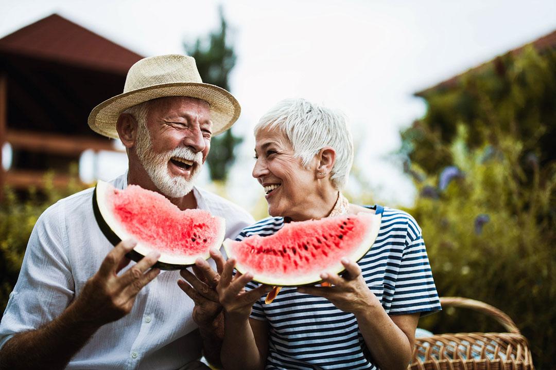 senior couple eating watermelon in summer