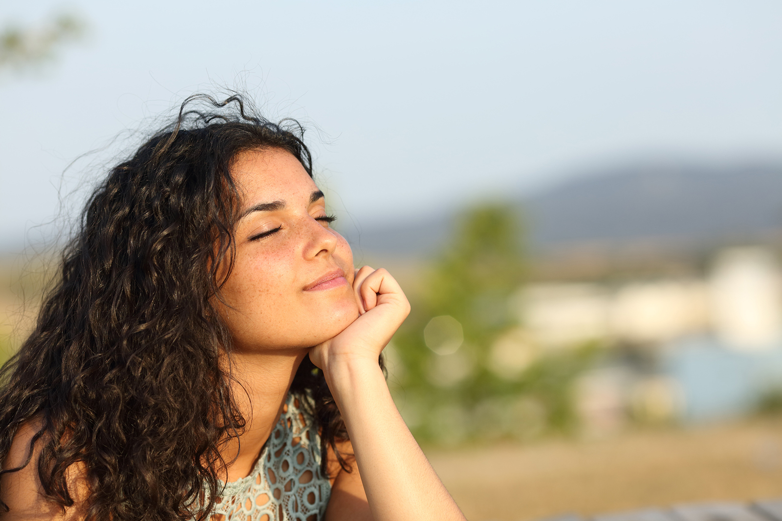 Mujer, relajante, tomando vitamina D bajo el sol en el parque