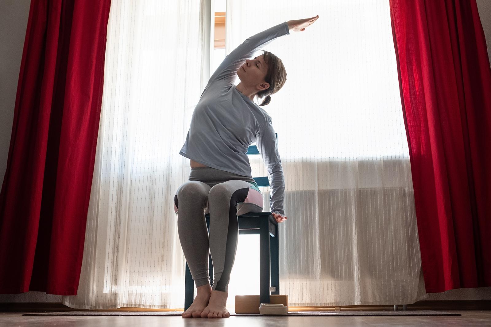 silla yoga estiramiento lateral - mujer haciendo yoga en casa