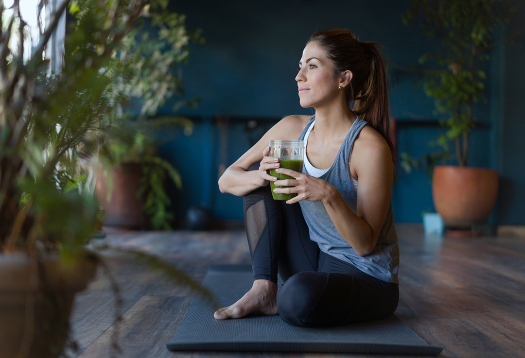 Mujer bebiendo suavizante verde para energía durante todo el día.